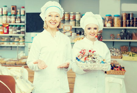 Photo for Friendly females staff offering sweets in local confectionery - Royalty Free Image