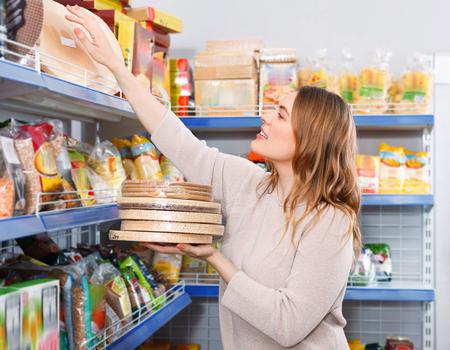 Foto de Adult cheerful  woman customer choosing biscuit layers in  grocery food store - Imagen libre de derechos