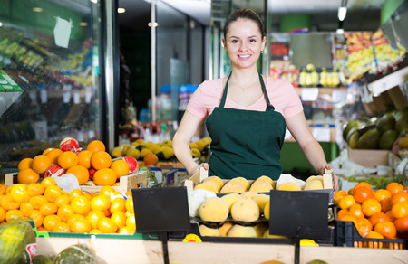 Photo for Smiling saleswoman standing behind the counter with ripe fruit on the market - Royalty Free Image