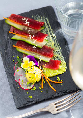 Photo for Slices of raw tuna sashimi served on black board with cucumber and sauce of avocado - Royalty Free Image