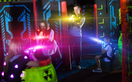 Photo for Modern young parents and children playing laser tag in dark labyrinth in bright beams of laser pistols - Royalty Free Image