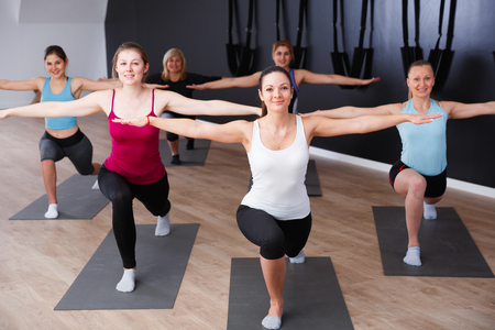 Photo for Group of young females exercising during yoga class at gym - Royalty Free Image