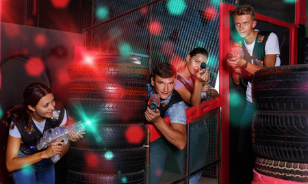 Photo for Smiling diligent positive cheerful glad  friends playing laser tag  game with colored laser guns near tires in labyrinth - Royalty Free Image