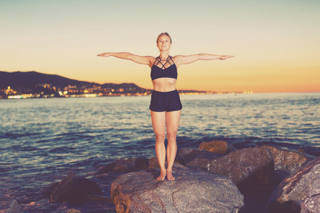Photo pour Woman is practicing stretching on a rock near sea at the dawn. - image libre de droit