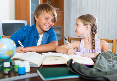 Photo pour Cheerful big brother helping little sister to do homework at home - image libre de droit