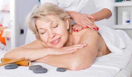 Foto de Aged smiling woman having professional massage in spa salon - Imagen libre de derechos