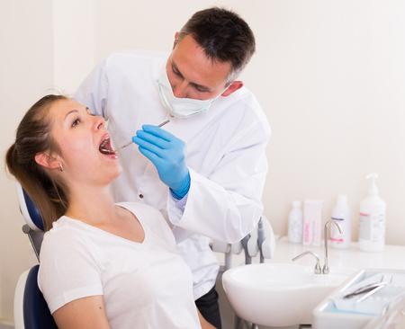 Foto de Dentist is treating woman patient which is sitting in dental chair in clinic. - Imagen libre de derechos