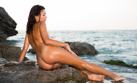 Photo pour Young nude woman sitting gracefully on rock against sea back to viewer - image libre de droit