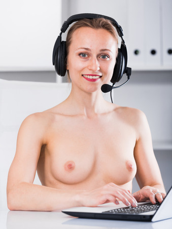 Foto per Young smiling naked girl talking on the headset in the office - Immagine Royalty Free