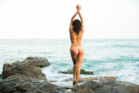 Photo pour Portrait of absolutely naked girl standing in sensual pose on rock near sea - image libre de droit