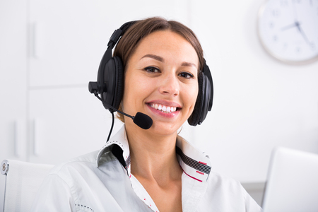 Photo pour portrait of cheerful woman with headset on answering at company office - image libre de droit