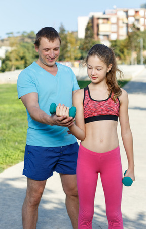 Foto de Slim tweenager girl performing physical exercises with dumbbells during daily workout with her father outdoors - Imagen libre de derechos