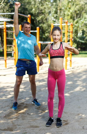 Foto de Happy tween girl stretching together with father during training outdoors in summer day - Imagen libre de derechos