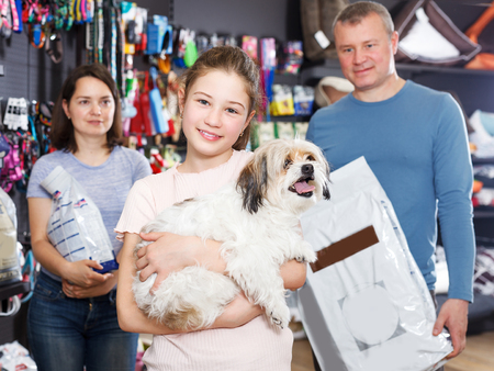 Foto de Portrait of cheerful girl with havanese pup while shopping with parents in pet store - Imagen libre de derechos