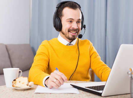 Photo pour Young male student studying at online courses productively at home - image libre de droit
