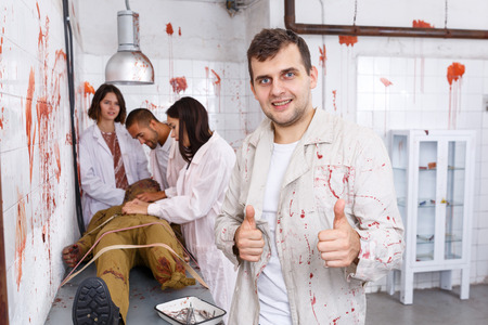 Foto de Portrait of cheerful guy with friends in quest room with bloody traces on walls and zombie mannequin on surgical table - Imagen libre de derechos