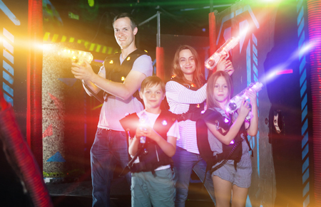 Foto per Excited kids and theirs parents in bright beams of laser guns during laser tag game in dark room - Immagine Royalty Free