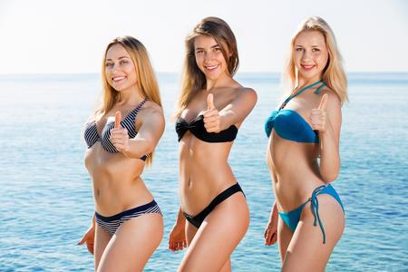 Foto de Portrait of three beautiful positive young women in swimsuits on  beach - Imagen libre de derechos