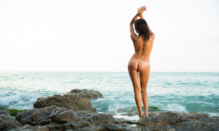 Photo pour Back view of sexy naked woman standing on stones at  ocean shore alone - image libre de droit
