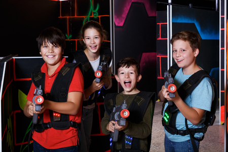 Photo for Portrait of happy excited teen kids with laser guns during lasertag game in dark room - Royalty Free Image