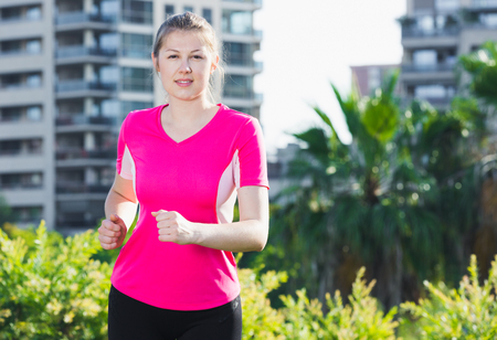 Photo for Sporty woman in pink T-shirt is jogging around the urban. - Royalty Free Image