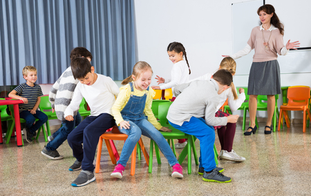 Foto de Happy laughing pupils of primary school having fun during break with their teacher, playing musical chairs - Imagen libre de derechos