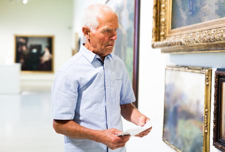 Foto de Intelligent mature tourist holding brochure with exhibition program near paintings in modern museum - Imagen libre de derechos