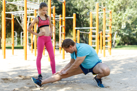 Photo pour Happy family of father and preteen girl stretching together after training outdoors - image libre de droit