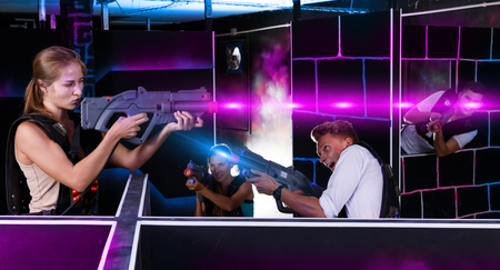 Photo for Laser tag players standing opposite each other with laser guns in dark room - Royalty Free Image
