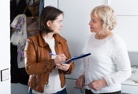 Photo for Interviewer interviews a mature woman at home, a social or commercial survey - Royalty Free Image