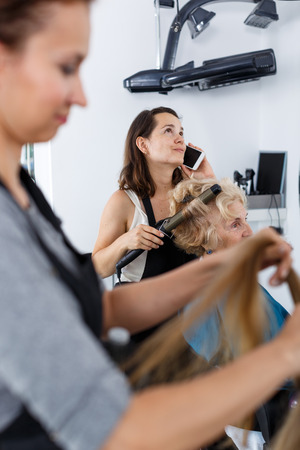 Photo for Distracted hairdresser emotionally talking on phone while making styling of senior woman at barbershop - Royalty Free Image