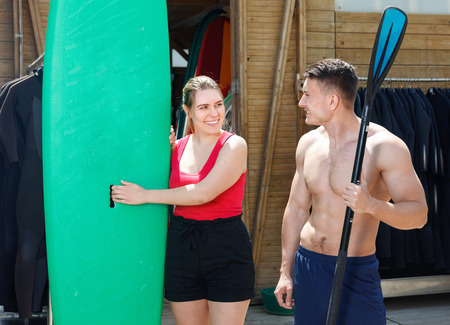 Young  friendly  couple planning to surf, choosing boards and surfing suits in beach club