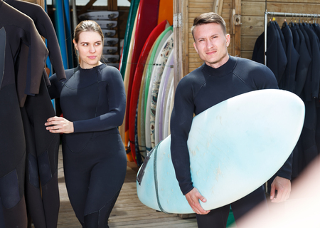 Young sporty couple in wetsuits choosing surf equipment in surf club