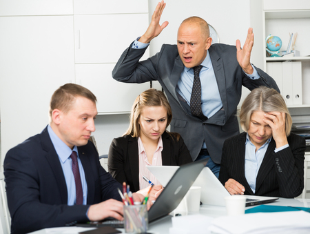 Photo for Group of sad frustrated employees receiving rebuke, suffering from bad attitude of shouting executive at work - Royalty Free Image