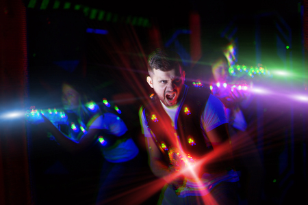 Foto per Portrait of excited guy laser tag player with laser pistol in room with bright beams - Immagine Royalty Free