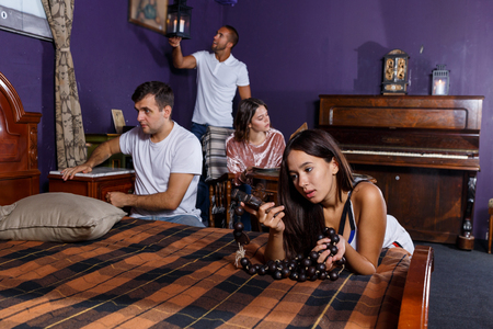 Foto de Young people looking at old wooden rosary while pursuing investigation in escape room with antique furniture - Imagen libre de derechos