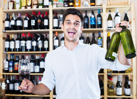 Foto de Cheerful man holding glass and bottle in winery section in store - Imagen libre de derechos