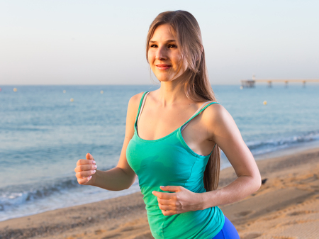 Photo for Female in blue T-shirt is jogging on the beach. - Royalty Free Image