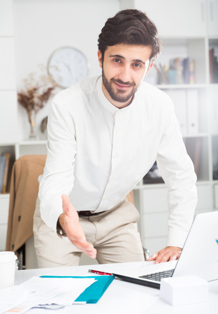 Photo for Young positive man manager offering to shake hand at office - Royalty Free Image