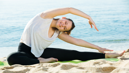 Photo for Smiling adult female in white T-shirt is practicing set of stretching exercises on nature. - Royalty Free Image