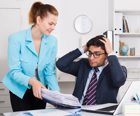 Photo for Overworked businessman looking at female colleague bringing new sheaf of papers - Royalty Free Image