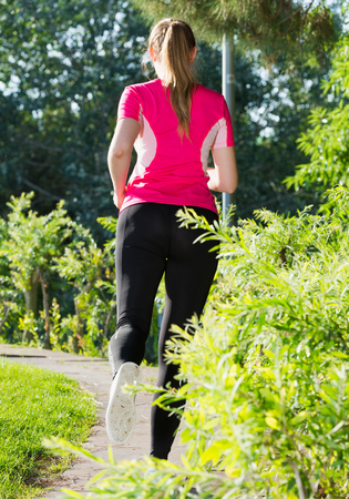 Photo for Adult female in pink T-shirt is jogging back in the park. - Royalty Free Image