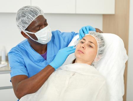 Foto de Male doctor in mask is doing injection to woman patient in skin of face in estetic clinic - Imagen libre de derechos