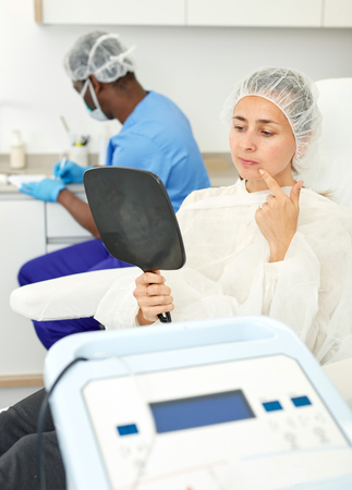 Foto de Woman sitting in armchair and looking to mirror before procedure in clinic of esthetic cosmetology - Imagen libre de derechos