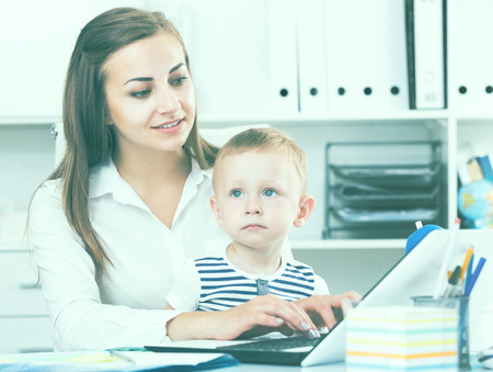 Photo pour Smiling woman with child is productively working behind laptop in office. - image libre de droit