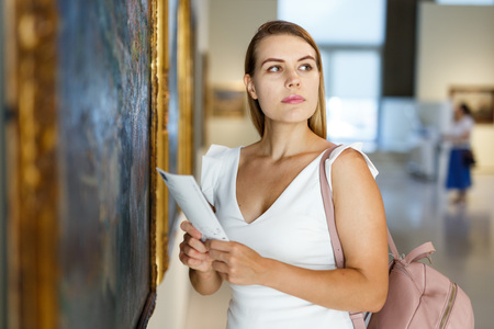 Foto de Portrait of attractive girl with guide brochure looking at paintings in art museum - Imagen libre de derechos