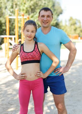 Foto de Smiling sporty man and tweenager girl posing together while exercising in summer park - Imagen libre de derechos