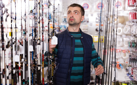 Young purchaser selectioning fishing rod in the sports shop indoors