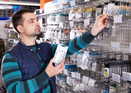 enthusiastic male customer choosing fishing hooks near stand in the sports shop indoors