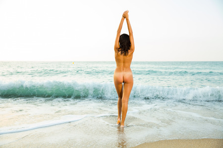 Photo pour Back view of sexy nude girl playfully posing  on the sandy beach - image libre de droit